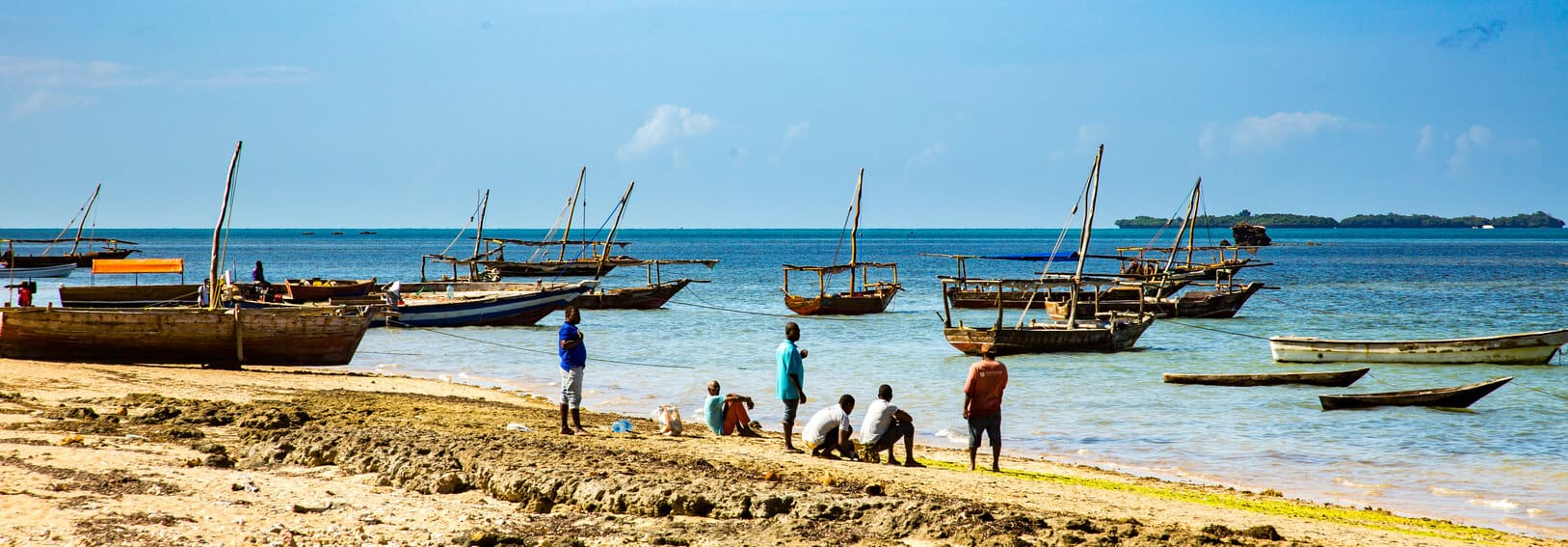 Fishing boats tied up along the shore of the Indian Ocean.